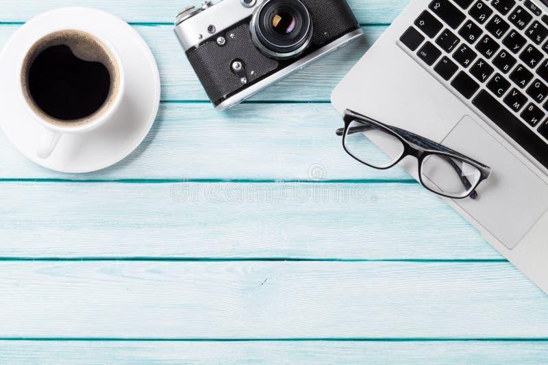 Table de bureau avec l'ordinateur portable et l'appareil-photo image stock