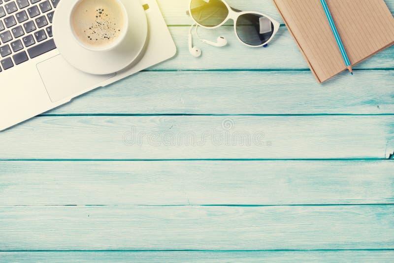 Table de bureau avec l'ordinateur portable, le café et les lunettes de soleil image stock