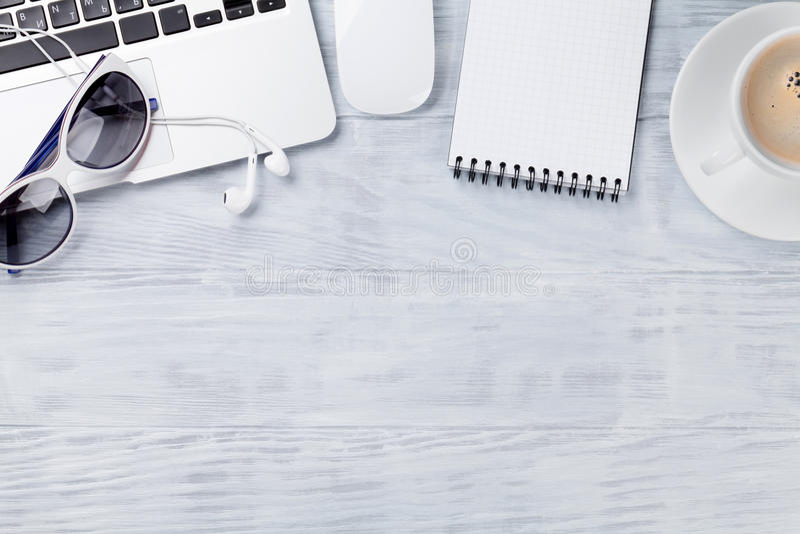Table de bureau avec l'ordinateur portable, le café, le bloc-notes et les lunettes de soleil image libre de droits