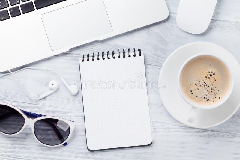 Table de bureau avec l'ordinateur portable, le café, le bloc-notes et les lunettes de soleil images libres de droits