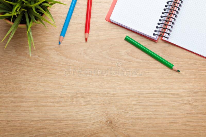 Table de bureau avec la fleur, le bloc-notes vide et les crayons colorés images libres de droits