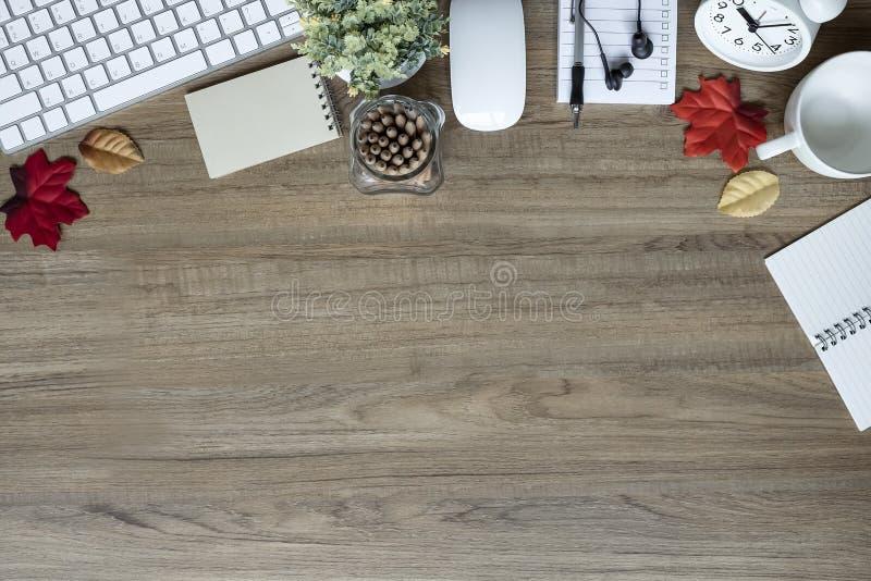 Table de bureau avec la tasse de clavier, d'approvisionnements, de fleur et de café photographie stock libre de droits