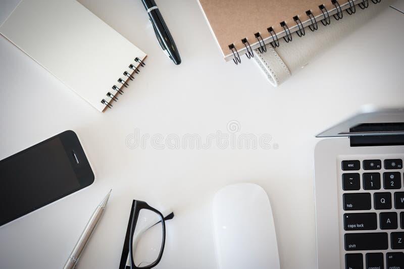 Table de bureau avec la tasse d'ordinateur, d'approvisionnements, de fleur et de café photographie stock libre de droits