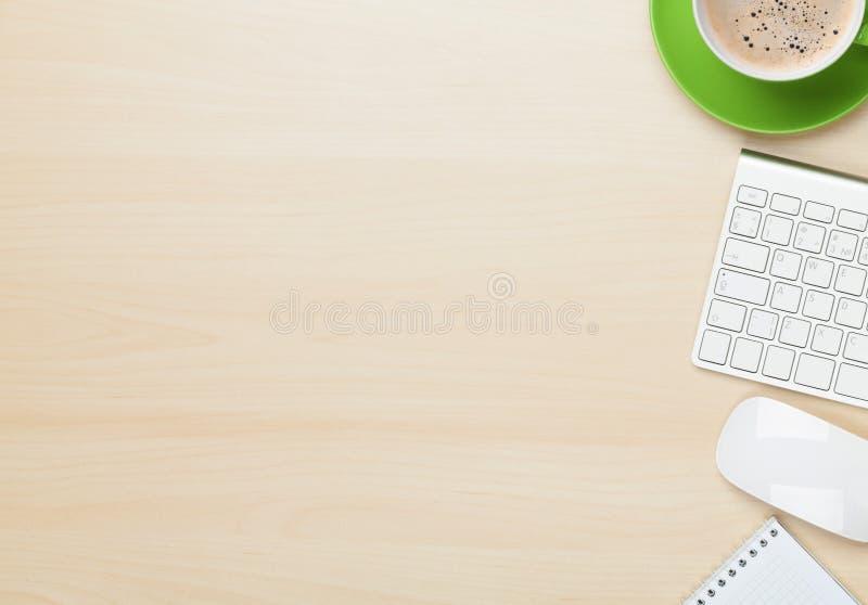 Table de bureau avec la tasse de bloc-notes, d'ordinateur et de café photo stock