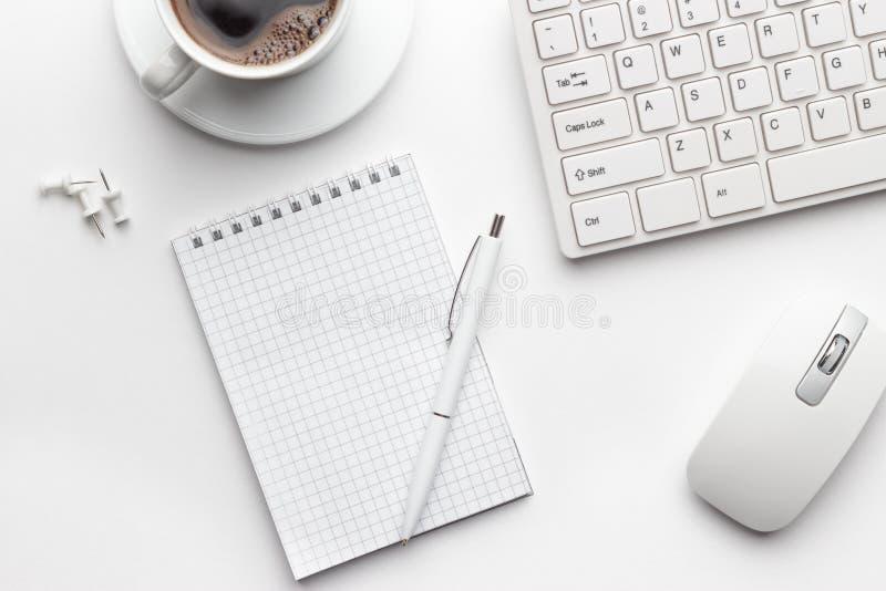 Table de bureau avec la tasse de bloc-notes, d'ordinateur et de café photographie stock libre de droits