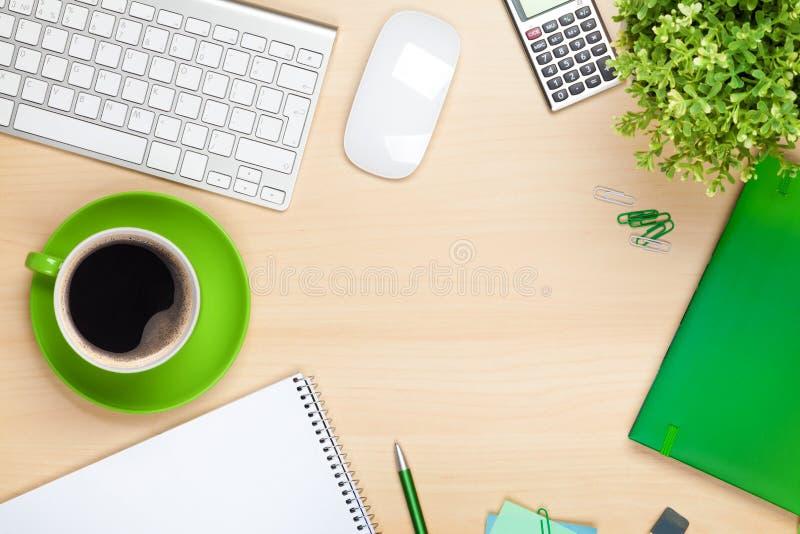 Table de bureau avec la tasse, l'ordinateur et la fleur de café photo libre de droits