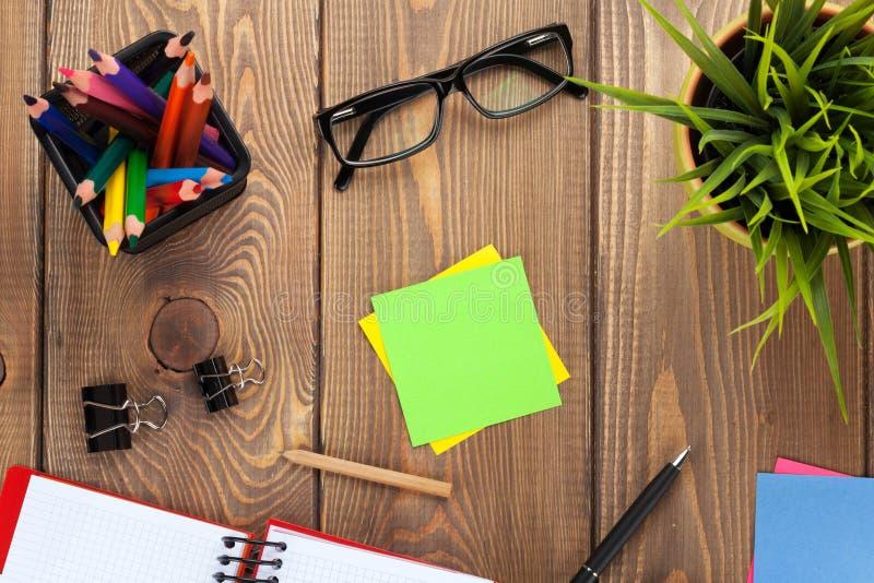 Table de bureau avec le bloc-notes, les crayons colorés, les approvisionnements et la fleur photos libres de droits