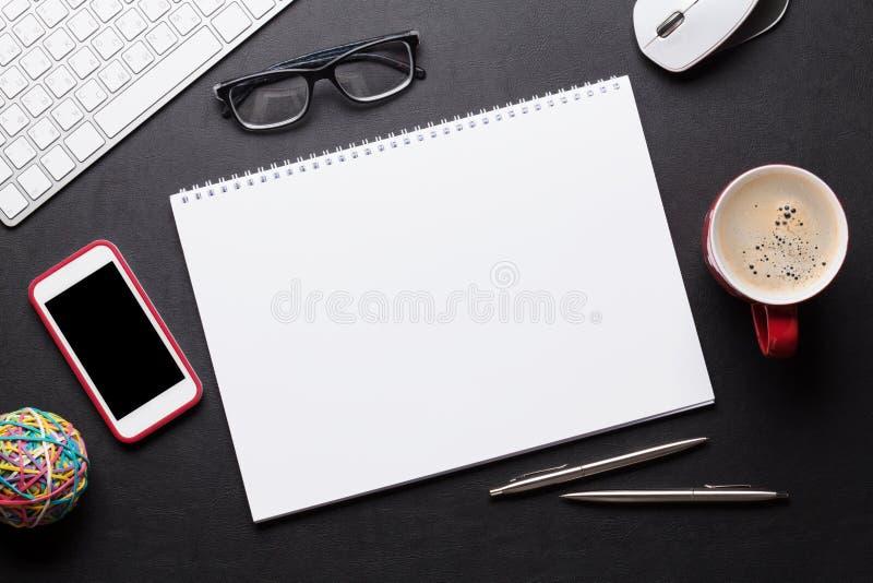 Table de bureau avec le PC, le bloc-notes, les verres, le café et le téléphone photos stock