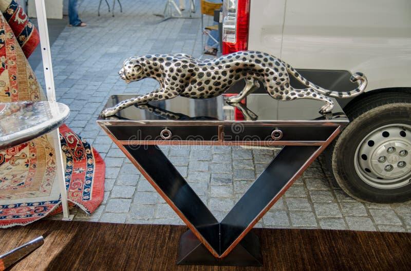 table de cru avec une sculpture en guépard au marché aux puces, France photos stock