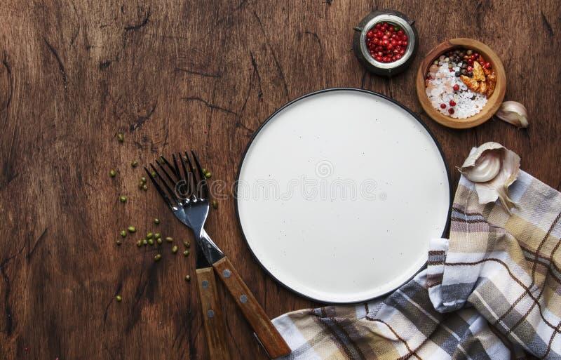 Table de cuisine en bois de cru, mangeant, faisant cuire le fond de nourriture vide avec le plat blanc, fourchettes, épices, serv photographie stock libre de droits