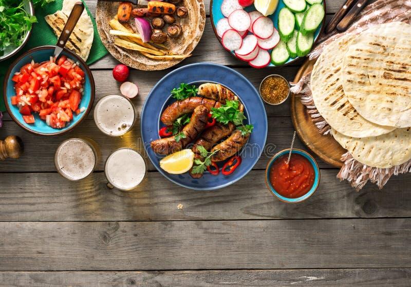 Table de dîner avec la saucisse, la tortilla, la bière et différent grillés photographie stock libre de droits