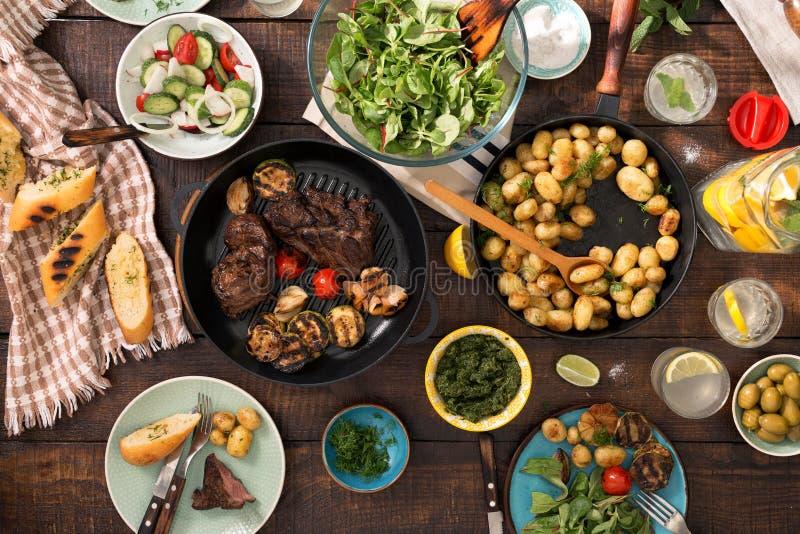 Table de dîner avec le bifteck grillé, légumes, pommes de terre, salade, Sn photos stock