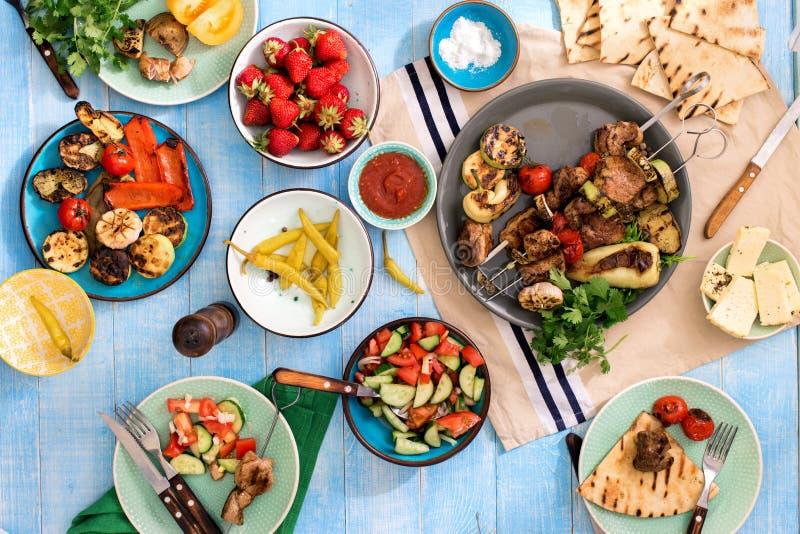 Table de dîner avec le chiche-kebab, légumes grillés, salade, casse-croûte image stock