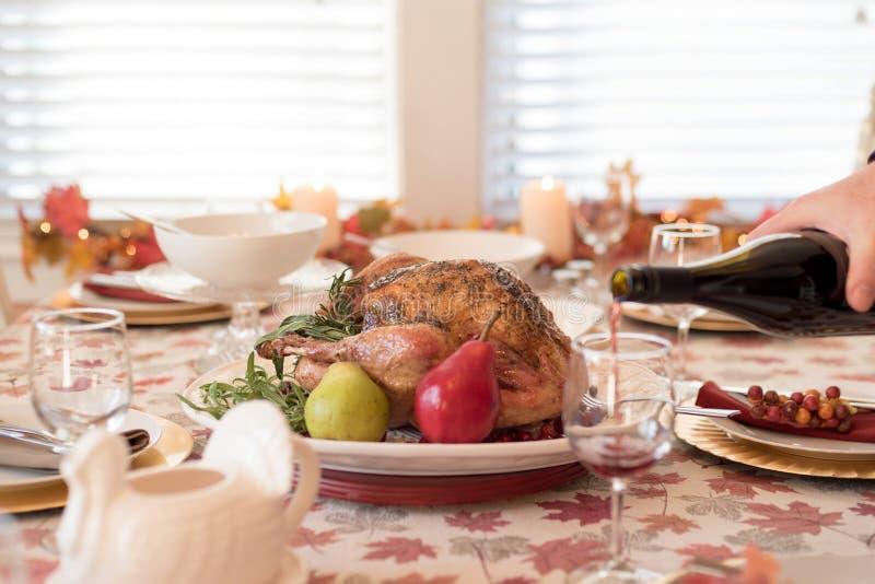 Table de dîner de vacances avec la dinde rôtie, homme versant le vin rouge dans le premier plan photo libre de droits