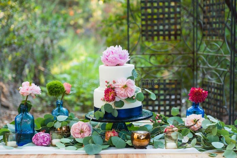 Table de dessert avec gâteau de mariage et fleurs photographie stock libre de droits