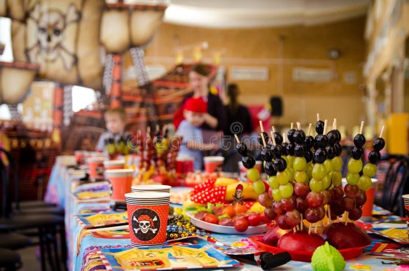 Table de fête couverte dans le symbolisme de pirate avec la nourriture sur une partie de pirate photo stock