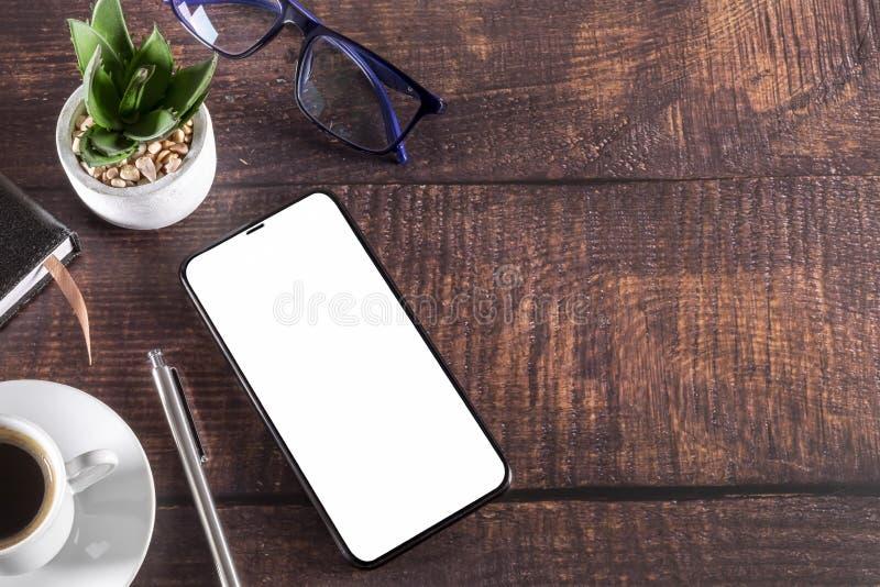 Table de fonctionnement avec l'usine en verre de stylo de tasse de café de bloc-notes de smartphone sur en bois photographie stock