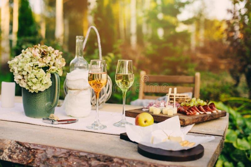 Table de jardin d'été décorée des fleurs et des bougies, soirée avec du vin images libres de droits