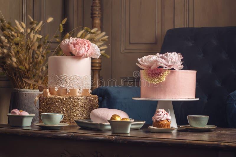 Table de luxe de mariage avec un beau gâteau rose décoré du mastic et de l'or rose dans l'intérieur classique antique image libre de droits