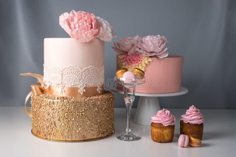 Table de luxe de mariage avec un beau gâteau rose décoré de la rose et de l'or de rose de mastic sur le fond gris image stock