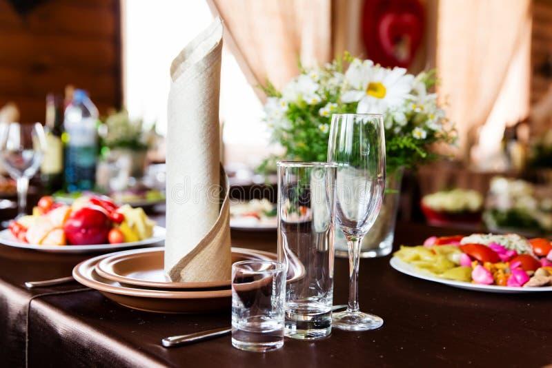 Table de mariage dans le restaurant avec la composition en fleur photos stock