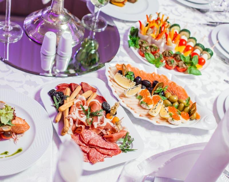 Table de mariage servie avec les repas savoureux, viande froide de plateau d'antipasto, plateau de poissons, plateau de fromage M photographie stock libre de droits
