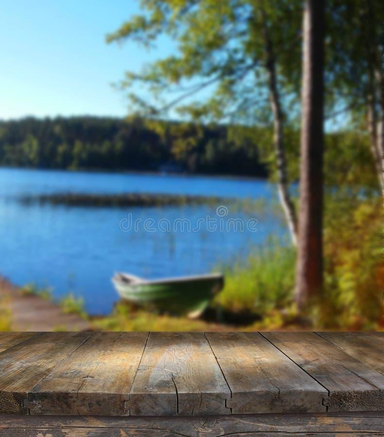Table de panneau en bois de vintage devant le paysage rêveur et abstrait de forêt et de lac avec la fusée de lentille images libres de droits
