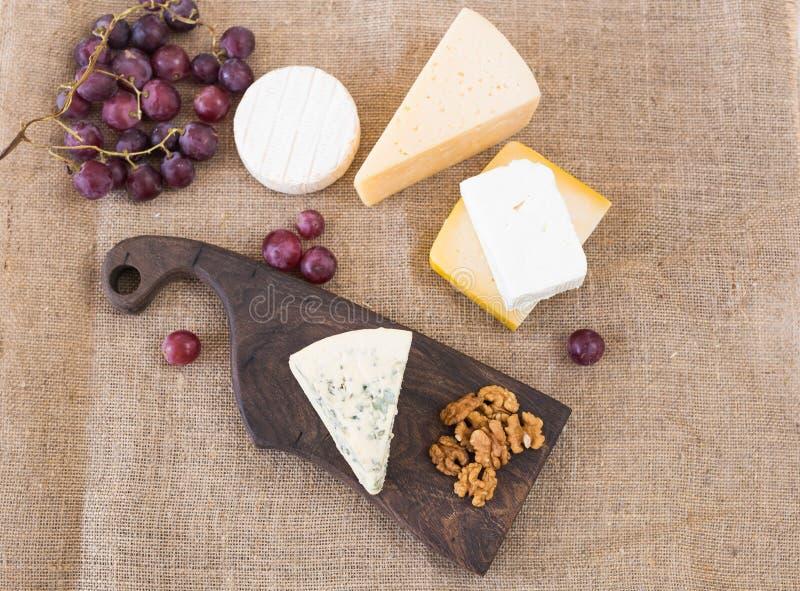 Table de partie de fromage, apéritif parfait de vacances avec l'écrou sur le conseil en bois rustique photos stock