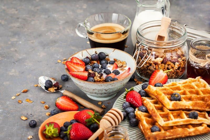 Table de petit déjeuner avec la granola de céréale, lait, baies fraîches, café photo libre de droits