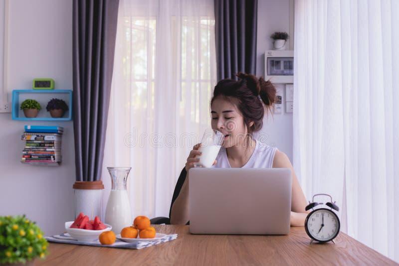 Table de petit déjeuner avec la jeune femme asiatique boire du lait dans le salon photos stock