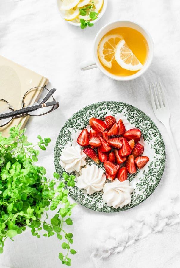 Table de petit déjeuner ou de casse-croûte - fraises fraîches, meringue, thé vert avec le citron De maison toujours la vie confor image libre de droits