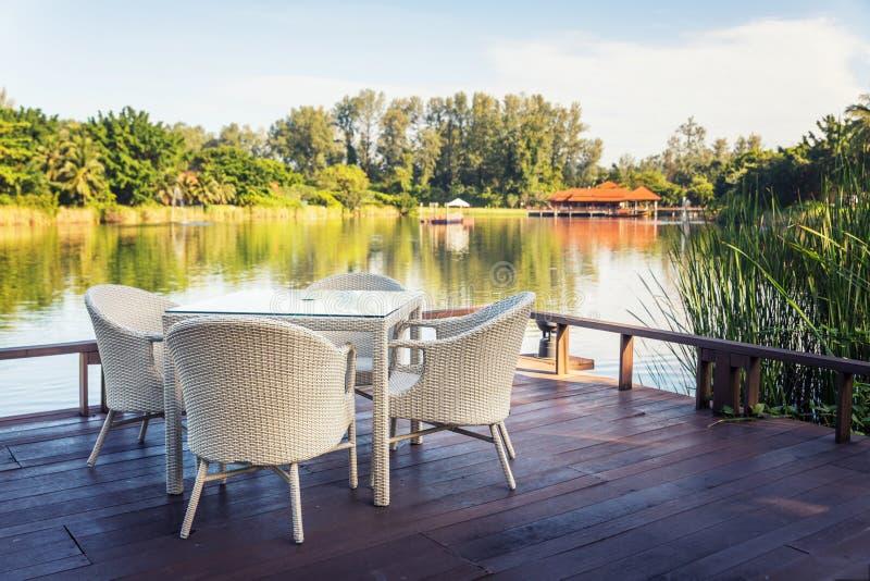 Table de salle à manger blanche extérieure de jardin par le côté de l'eau images stock