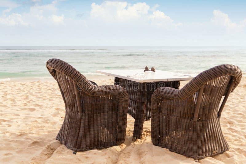 Table de salle à manger et deux chaises par le côté de mer image stock