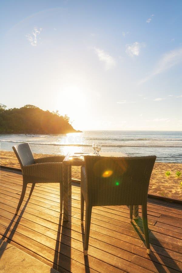 Table de salle à manger et deux chaises sur le decking par le côté de mer à égaliser le su images libres de droits