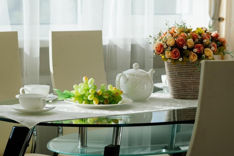 Table de salle à manger installée avec la vaisselle pour le thé, raisins, fleurs image stock