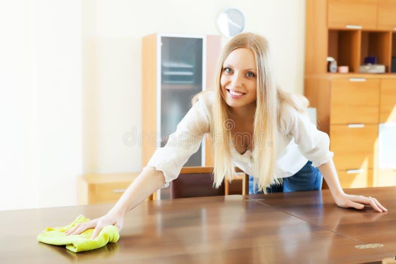 Table de sourire de nettoyage de femme à la maison image stock