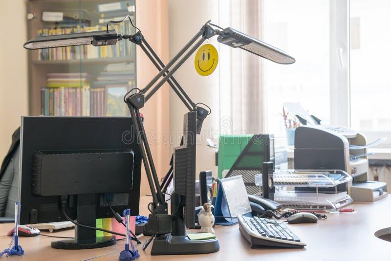 Table de travail dans le petit bureau avec la fenêtre et la bibliothèque image stock