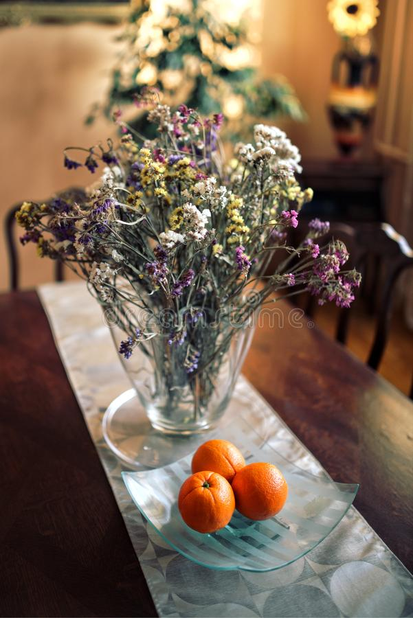 Table decor: flowers & oranges stock photography