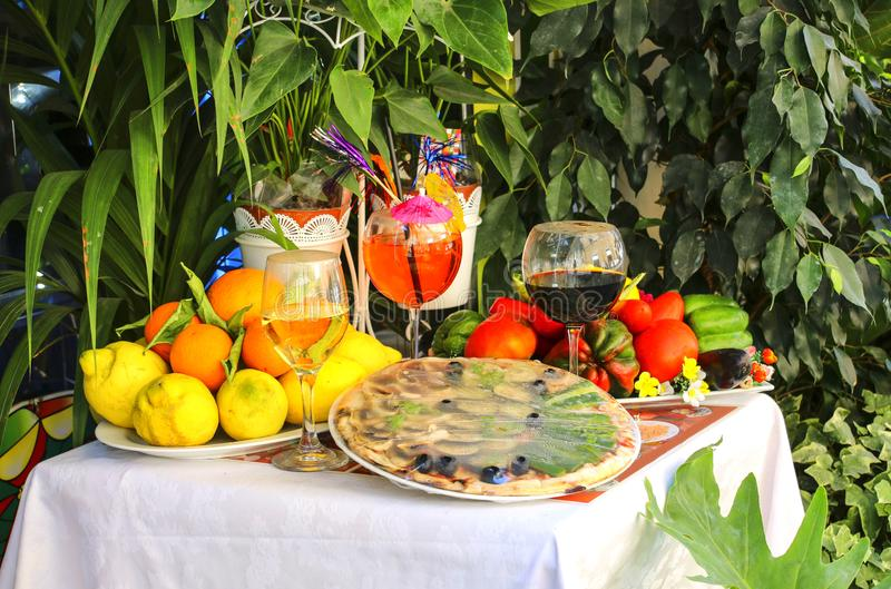 Table decorated with pizza, fruit and wine traditional Italian. Products in one of the markets of Rome, Italy royalty free stock image