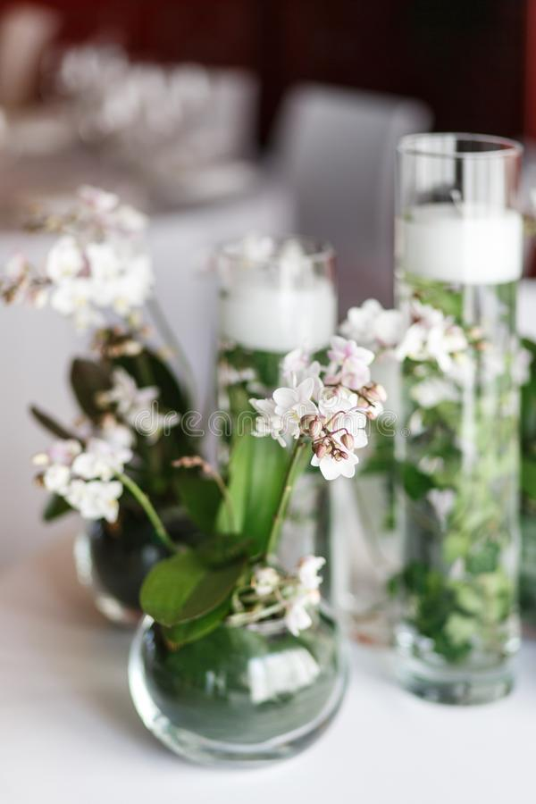 The table is decorated with vases and lily of the valley flowers stock photo