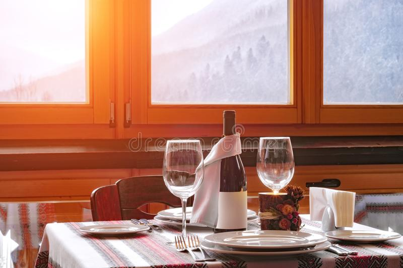 Table decoration with wine and candie. Against carpathian winter background. Romantic composition stock photo