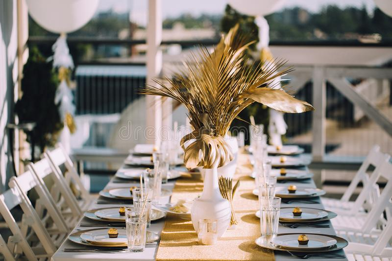 Table decorations with gold-plated plants and plates royalty free stock photo