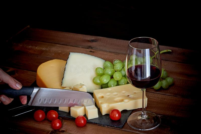 Table with different cheeses and wine glass on dark background royalty free stock image