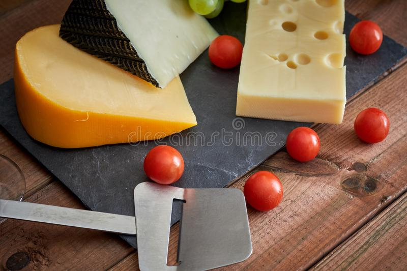 Table with different cheeses and wine glass on dark background royalty free stock images