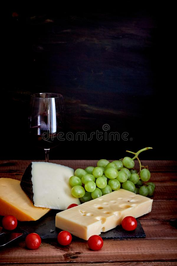 Table with different cheeses and wine glass on dark background royalty free stock photos