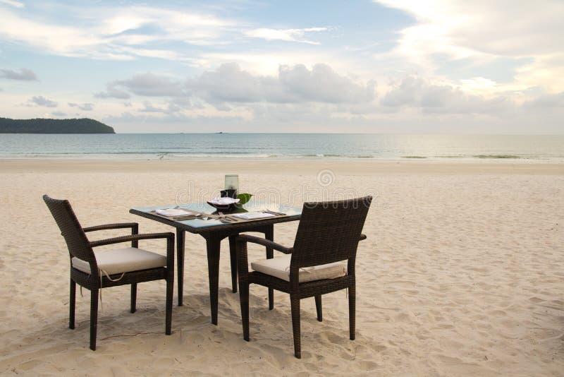 Table dinante sur la plage photos stock