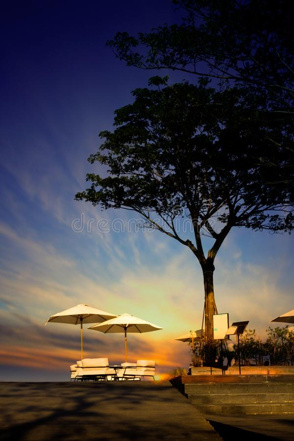 Table dinner with beach umbrellas setting outdoor and big tree silhouette in restaurant at the beach on twilight time bac stock images