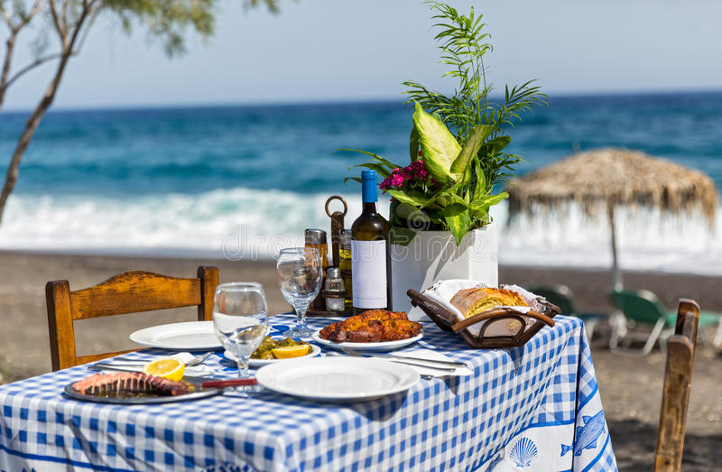 Table for dinner on the sand beach royalty free stock image