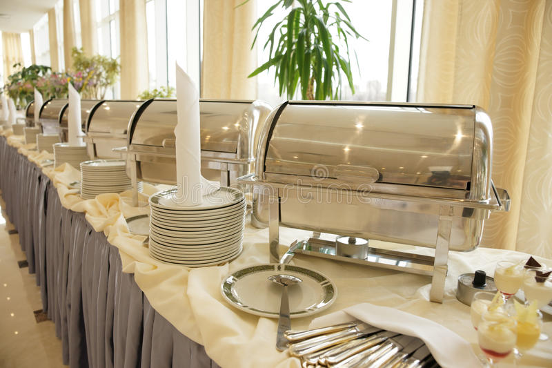 Table with dishware and shiny marmites