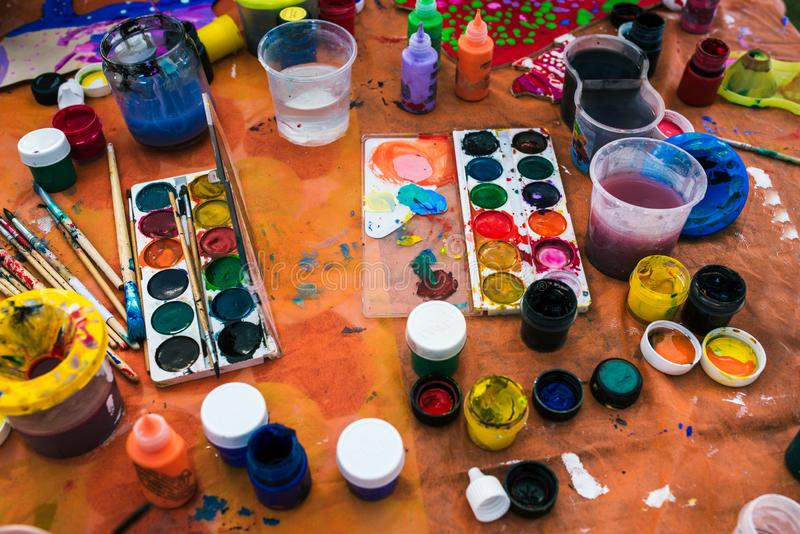 Table for drawing on which are brushes, paints, cans of water and a palette. The creative process. The concept of fine. Art, creativity and drawing. Artist royalty free stock photography